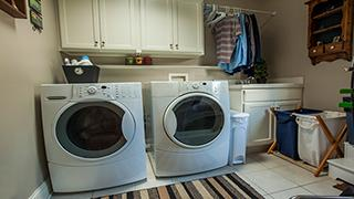 Laundry room with washer, dryer, and hanging clothes.