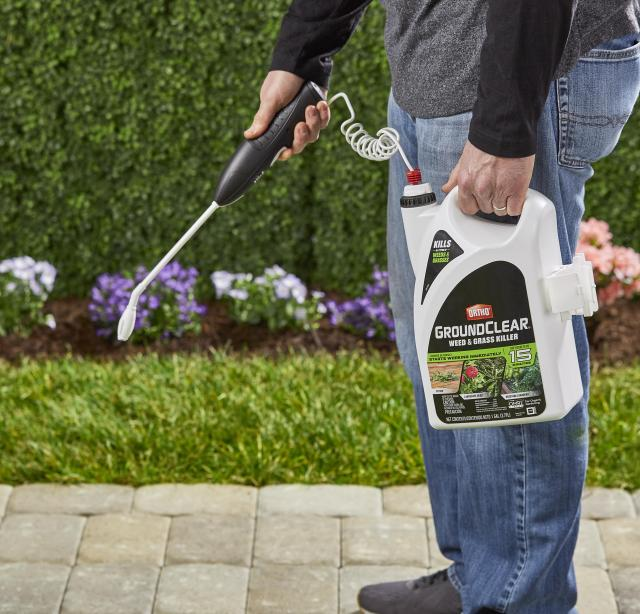 COnsumer using wand to spray sidewalk with product