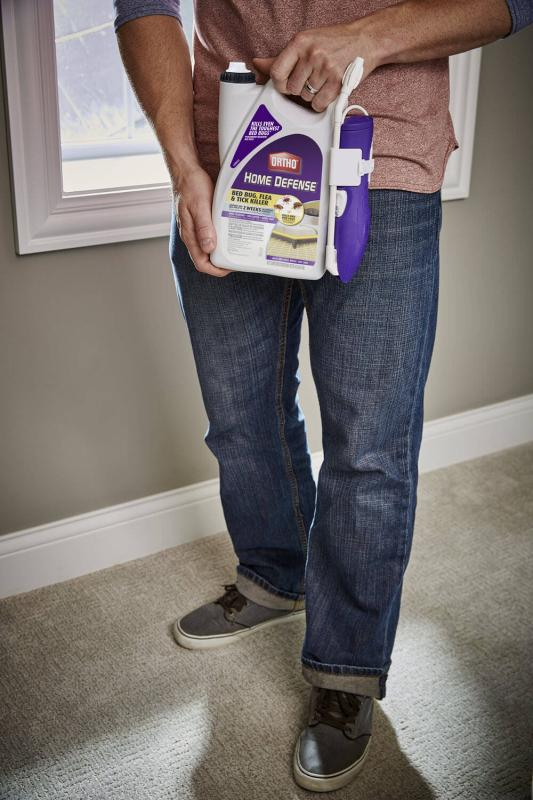 Man holding container of Ortho Home Defense Bed Bug, Flea & Tick Killer